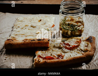 Potato pizza slices on baking tray sprinkled with olive oil infused with rosemary and garlic - Stock Photo