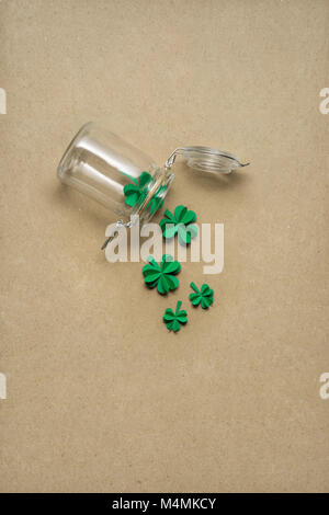 Creative St. Patricks Day concept photo of a bottle with shamrocks made of paper on brown background. - Stock Photo