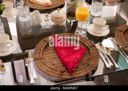 A glass table setting for brunch with glasses, cups, saucers, utensils, wicker placemats, and folded cloth napkin - Stock Photo