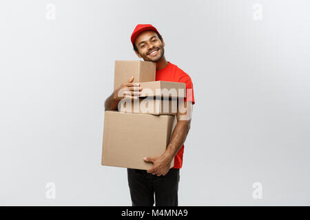 Delivery Concept - Portrait of Happy African American delivery man in red cloth holding a box package. Isolated - Stock Photo