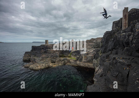 Cliff jumping into the Blue Pool, Portrush, County Antrim, Northern Ireland. - Stock Photo