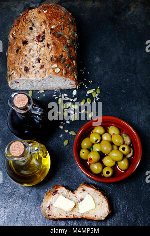 Fresh pumpkin seed bread with olive oil and butter from above - Stock Photo
