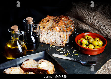 Fresh pumpkin seed bread with olive oil and butter - Stock Photo