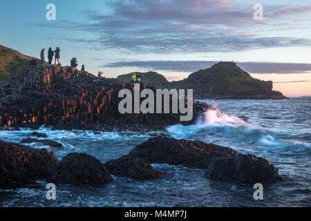 Evening visitors at the Giant's Causeway, Country Antrim, Northern Ireland. - Stock Photo