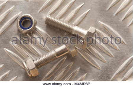 Bolts with nuts on metal surface - Stock Photo