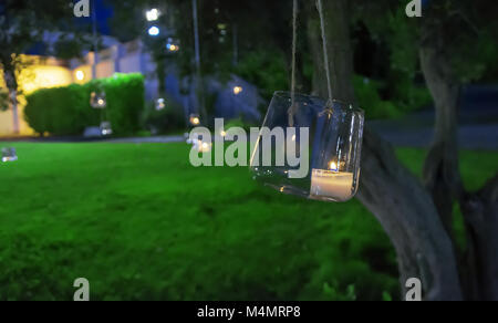 candle in a glass hanging from a tree - Stock Photo