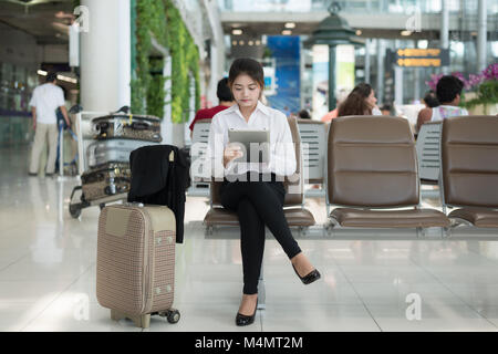 Asian young woman passenger at airport, using her tablet computer while waiting for her flight in terminal at airport. - Stock Photo