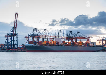 Industrial Container Cargo freight ship with working crane bridge in shipyard at Rotterdam, Netherlands. for Logistics Import Export background.