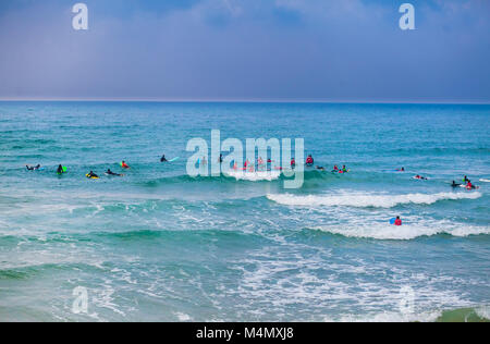 Surfing school class taking place in the water at sunset - Stock Photo