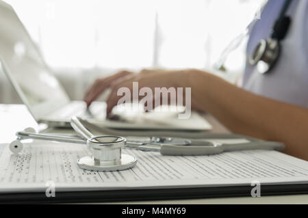 Close-up of a doctor typing on keybord in the office - Stock Photo