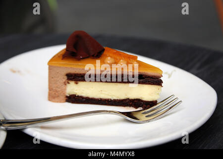 A slice of chocolate orange mousse cake on plate with fork at cafe - Stock Photo