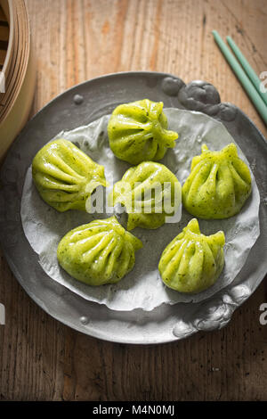Steamed edamame dim sum. Sticky spinach & rice dumplings, filled with edamame, mint and water chestnuts - Stock Photo