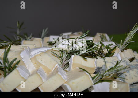 Zoom on some cheese decorated with rosemary - Stock Photo