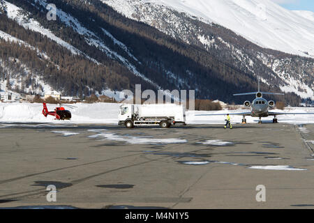 A red helicopter, a fuel truck and a private jet in the airport of St Moritz in the snowy alps switzerland in winter - Stock Photo