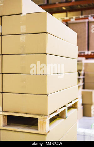 stack of boxes and cartons on wooden pallet in warehouse - Stock Photo
