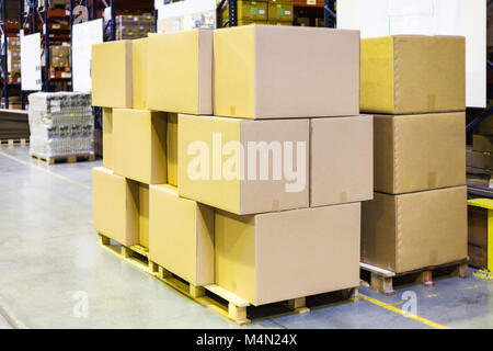 packaged boxes and cartons on wooden pallets in warehouse - Stock Photo