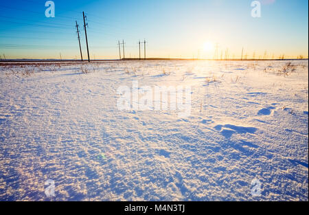 Winter landscape in a field covered with snow on a background of sunset and poles with power lines - Stock Photo