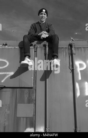 Black and White Industrial Portrait of a Young Man Atop an Old Shipping Container at Cruden Bay Harbour, Aberdeenshire, - Stock Photo