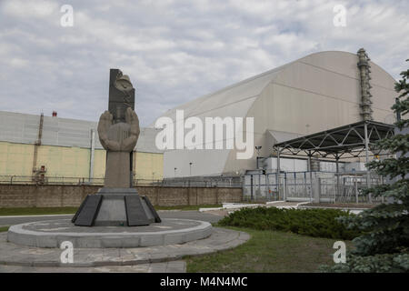Memorial near reactor number four in Chernobyl stands infront of the new safe confinement  sarcophagus - Stock Photo