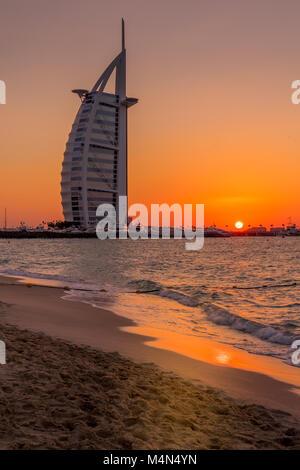 Sunset view of Burj Al Arab hotel on Jumeirah beach in Dubai, United Arab Emirates - Stock Photo