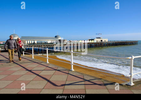 Hastings, East Sussex UK. A couple strolling along the promenade under a cloudless blue sky on a mild sunny day - Stock Photo