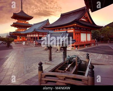 Beautiful sunrise scenery of Kiyomizu-dera Buddhist temple buildings. Chozubachi, water ablution pavilion, basin - Stock Photo