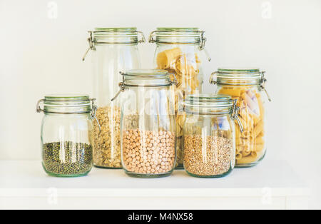 Various raw cereals, grains, beans and pasta for healthy cooking in glass storage jars on kitchen shelf, white background. - Stock Photo