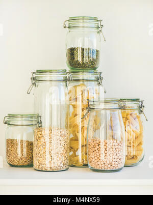 Various raw cereals, grains, beans and pasta for healthy cooking in glass jars on kitchen shelf, white background. - Stock Photo