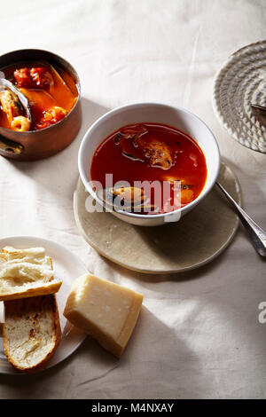 Traditional mediterranean soup bouillabaisse with mussels, shrimps, tomatoes and fish broth served in copper saucepan - Stock Photo