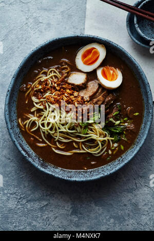 Vertical close up shot of japanese ramen with pork belly, mushrooms and marinated eggs served in blue handmade ceramic - Stock Photo