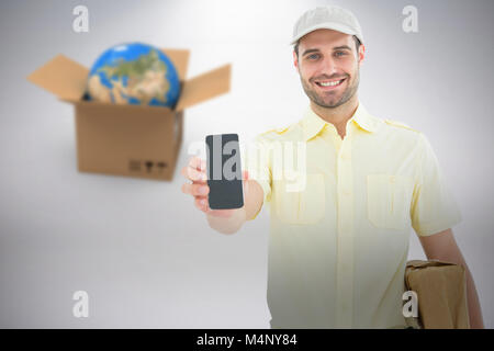 Composite 3d image of handsome delivery man showing mobile phone - Stock Photo