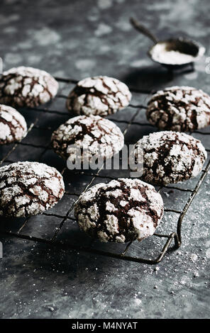 Chocolate crinkle cookies on wire cooling rack with icing sugar dusting. - Stock Photo