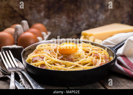 Pasta with bacon, egg and cheese on a wooden table - Stock Photo