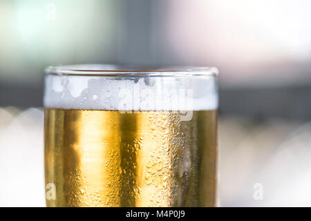 Macro detail shot of beer glass with foam lacing detail. Natural light on a sunny day. - Stock Photo
