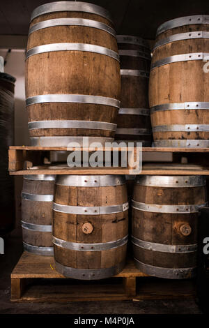 Pallets of beautiful, rustic, wine barrels in multiple sizes. - Stock Photo