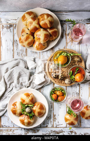 Easter table setting with colored orange eggs, hot cross buns, green branches decorated, empty plate, cutlery, glass - Stock Photo