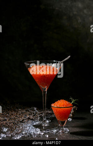 Two glasses of red caviar decorated by fresh rosemary on crushed ice over dark background. - Stock Photo