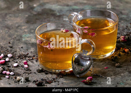 Two glasses of hot tea, rose buds, heart shaped tea strainer, pink sugar over old dark metal background. Space for - Stock Photo
