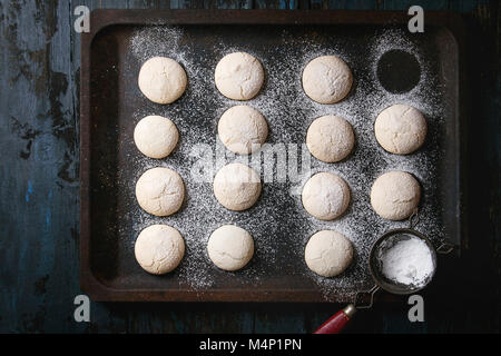 Homemade almond cookies with sugar powder, with vintage sieve, on old oven tray over dark blue wooden table. Dark - Stock Photo