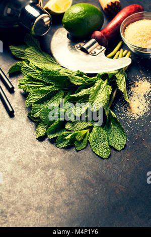Mojito cocktail ingredients (fresh mint, lime) on rustic background - Stock Photo