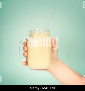 Womans hand holding smoothie shake against bright wall. Drinking  healthy smoothie concept - Stock Photo