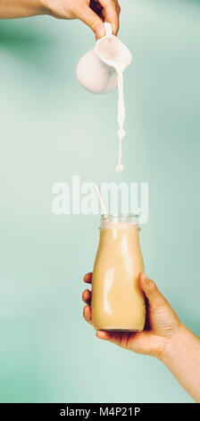 Womans hand holding smoothie shake against bright wall. Pouring milk into smoothie. Drinking healthy smoothie concept - Stock Photo
