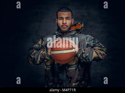 A black male in a camouflage hoodie holds basket ball. - Stock Photo