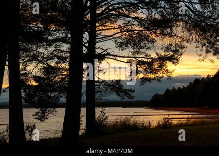 Beach at sunset by Orsa Lake in Orsa, Dalarna, Sweden. - Stock Photo