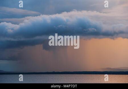 Rain cloud at sunset over Orsa lake in Dalarna, Swden. - Stock Photo