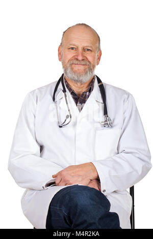 Smiling physician with white coat and stethoscope sitting on isolated background - Stock Photo