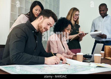 Young male architect writing on blueprints at a desk in a modern office with coworkers in the background - Stock Photo