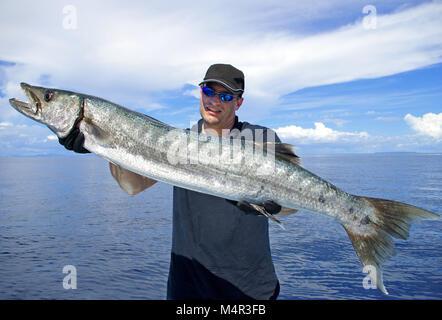 Happy  fisherman holding a beautiful baraccuda. Deep sea fishing, big game fishing, catch of fish. - Stock Photo