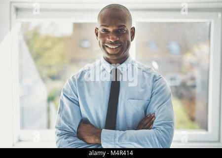 Smiling African businessman wearing a shirt and tie standing confidently with his arms crossed in his home office - Stock Photo