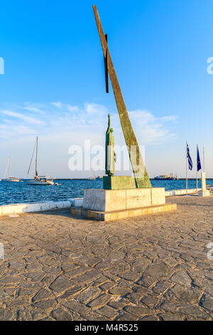 PYTHAGORION PORT, SAMOS ISLAND - SEP 18, 2015: statue in Pythagorion port at sunset time, Samos island, Greece. - Stock Photo